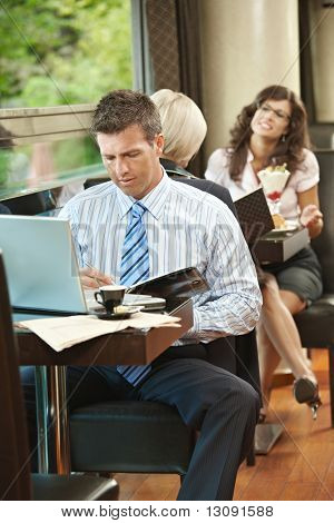 Businessman sitting at table in cafe using laptop computer, writing notes. Young women ordering sweets in the background.