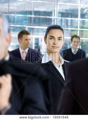 Young businesswoman standing amongt other businesspeople,in front of office building.