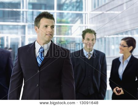 Young businessman standing in front of other businesspeople, out of office building.