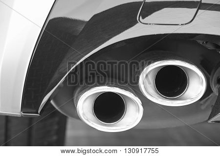 Double car exhaust pipe detail in black and white. Pollution. Horizontal