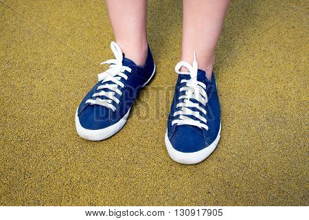 Female Feet In Blue Sneakers On Yellow Coating