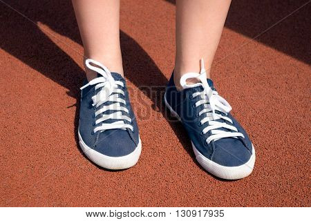 Female Feet In Blue Sneakers On A Sunny Day