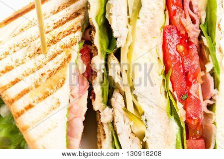 Traditional grilled club sandwich with chicken and tomatoes. Macro. Photo can be used as a whole background.