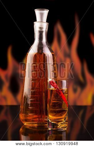 Bottle and a glass of vodka with red chili pepper on the background of flames.