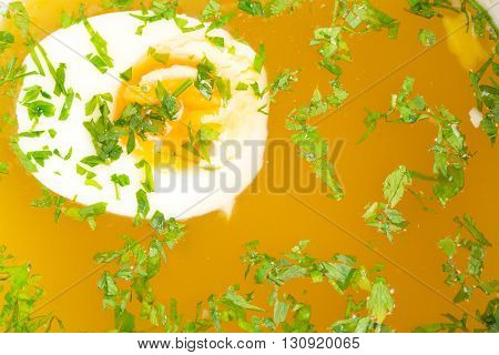 Chicken bouillon with egg and minced parsley. Macro. Photo can be used as a whole background.