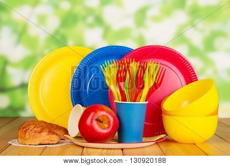 Bright disposable tableware, croissant and an apple on an abstract green background.