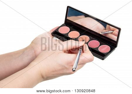 Cosmetic brush and set makeup in the hands of women isolated on white background.