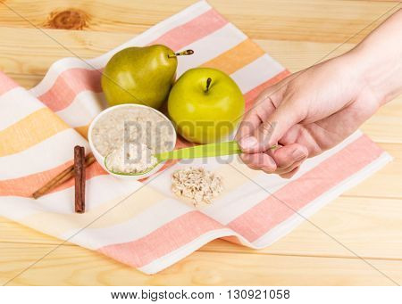 The female hand a spoon with porridge and fruits on a background of light wood.