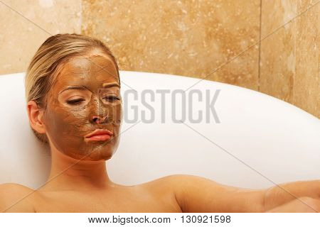 Woman sitting in a bath with closed eyes