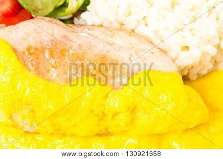 Roasted chicken fillet with rice and fresh vegetables as a garnish. Served with delicious saffron mousse. Macro. Photo can be used as a whole background.