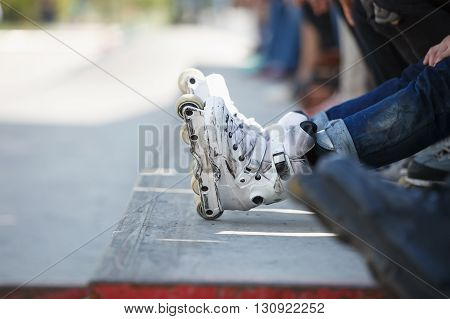 Aggressive Inline Rollerblader Sitting In Outdoor Skate Park