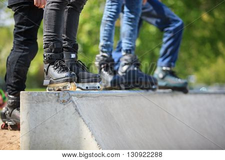 Feet of rollerblader wearing aggressive inline skates standing on top of concrete ramp in outdoor skate park. Extreme sports athlete wearing roller blades for tricks and grinds