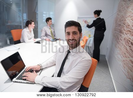 portrait of young modern arab business man with beard at office meeting room,   group of  business people  on brainstorming and  making plans and projects on white flip board in  background