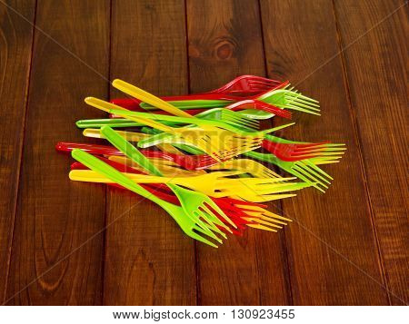 Colored plastic forks against the dark wood. Dishes.