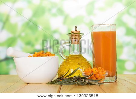 Buckthorn berries, oil bottle and a glass of juice on the abstract green background.