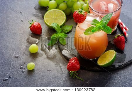 Strawberry summer refreshing drink with ice cubes lime mint. Homemade lemonade