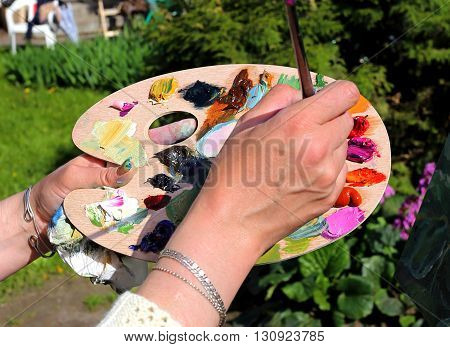 Hands of the artist in the preparation of oil paints on a palette