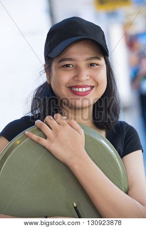Pretty Asian girl smiling  with tray in hand