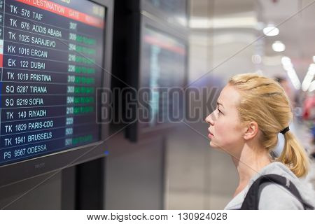 Young woman in international airport looking at the flight information board, checking her flight.