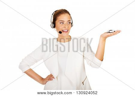 Young businesswoman in headset holding car toy