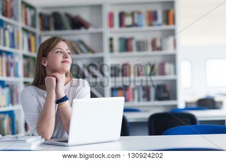 female student study in school library, using laptop and searching for informations on internet