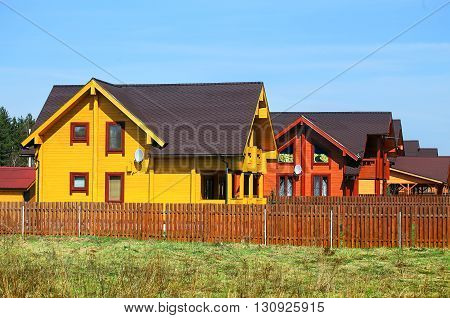 Settlement of wooden cottages of brown color surrounded by the fence