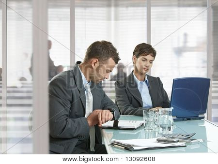 Businessman and businesswoman sitting at desk in office, using laptop computer and checking time.