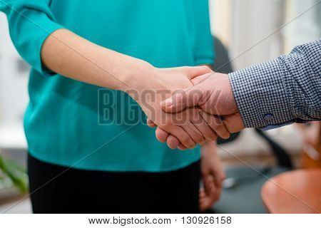 Closeup of business man and woman shaking hands in office setting on background