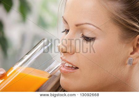 Closeup retrato da bela jovem beber suco de laranja.