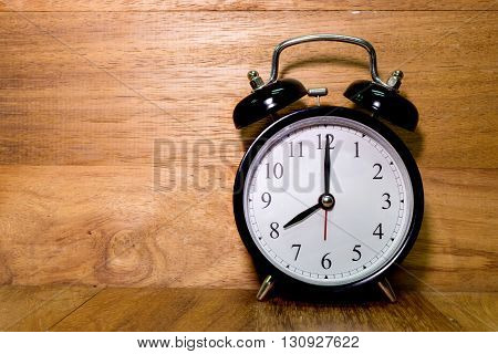 Vintage background with retro alarm clock on wood background Alarm clock shows Eight o`clock