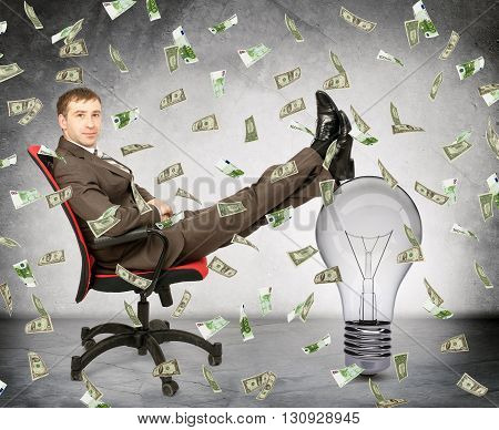 Businessman with light bulb and money rain, idea is money concept