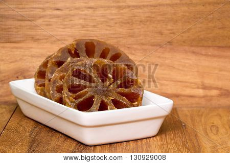 Fruit preserve slice in white plate on wood background