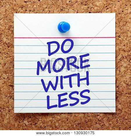 The words Do More With Less on a card pinned to a cork notice board as a reminder to increase productivity whilst saving money