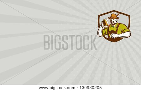 Business card showing illustration of a German Bavarian beer drinker raising beer mug for Oktoberfest toast wearing lederhosen and German hat set inside shield creest done in retro style.