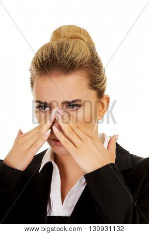 Young businesswoman suffering from sinus pain