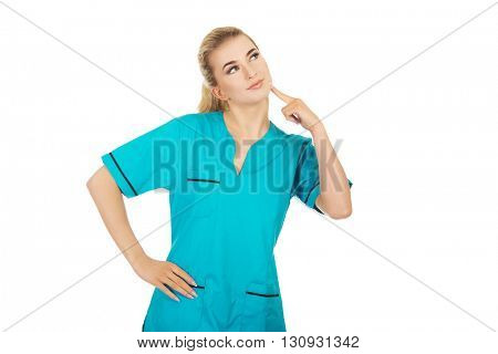 Smiling female nurse thinking about some idea