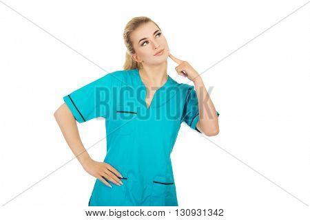 Smiling female nurse thinking about some idea