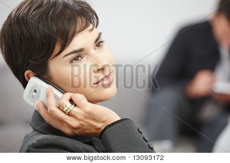 Young businesswoman sitting on sofa at office talking on mobile phone.
