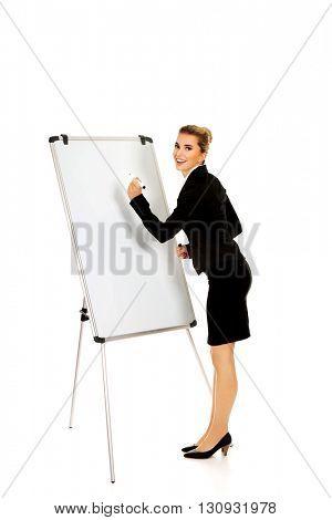 Smiling business woman writing on flipchart