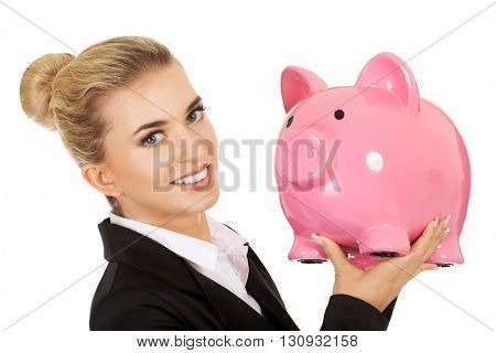 Young businesswoman saving money in piggybank