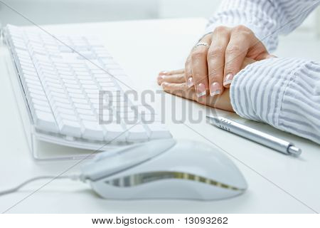 Closeup picture of female hands on desk, beside computer keyboard, mouse and pen.