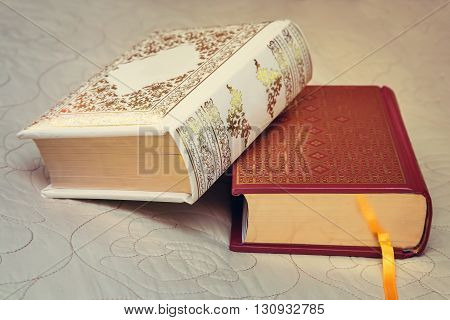 Two beautiful books lie on the couch in the background of a beautiful bedspread.