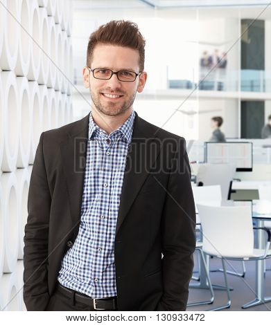 Portrait of young businessman standing hands in pockets, smiling, looking at camera.