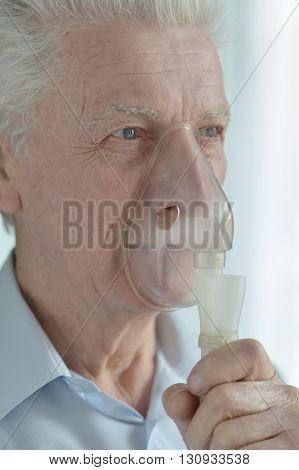 Portrait of an ill senior man with inhaler