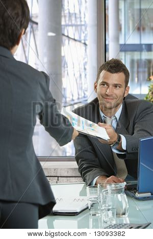 Businesspeople working in office. Smiling businessman handing over documents to businesswoman.