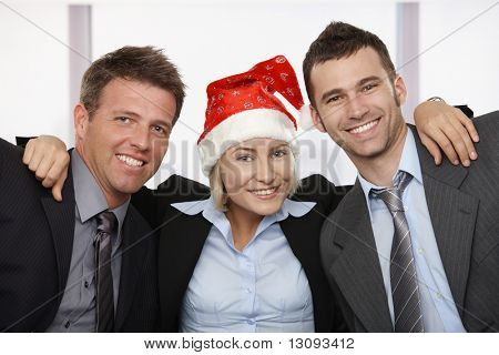 Happy young businesswoman wearing Santa Claus hat at office hugging friends, looking at camera, smiling.