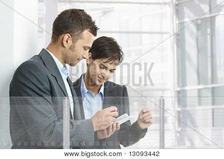 Two businesspeople standing in modern office building with glass walls, using smart mobile phone.