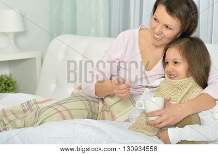 Sick little girl with mother in bed with hot drink at home