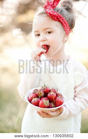 Cute kid girl 4-5 year old eating fresh strawberries outdoors. Holding white bowl with berries. Looking at camera. Summer season.