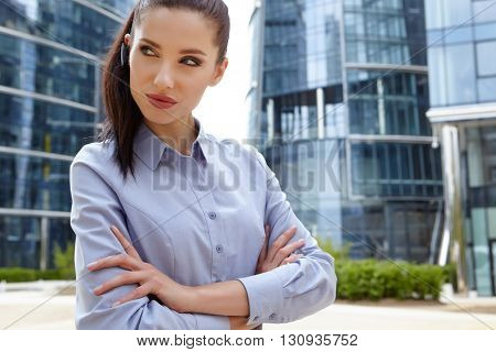 business, technology and people concept - smiling businesswoman with smartphone talking over office building